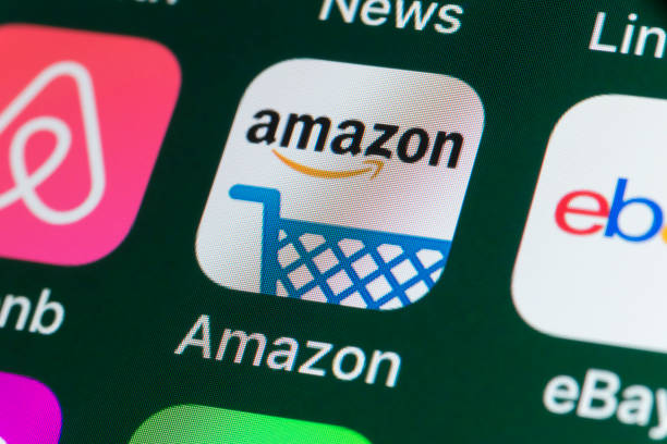 Amazon , Airbnb, ebay, News and other Apps on iPhone screen London, UK - July 31, 2018: The buttons of the online shopping app Amazon, surrounded by Airbnb, ebay, News and other apps on the screen of an iPhone. amazon stock pictures, royalty-free photos & images