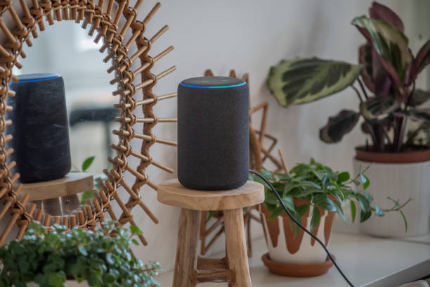 Amazon Alexa Echo Plus on a wooden table with green plants in the background stock photo