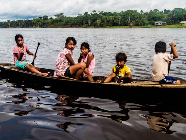 Amazon children in boat stock photo