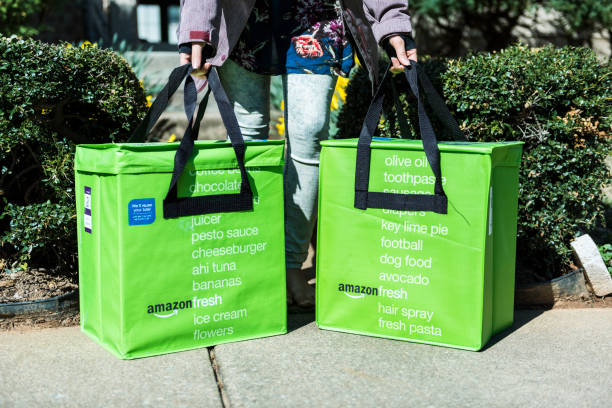 amazon fresh insulated grocery delivery bags on front porch closeup with woman picking them up - food logo stock photos and pictures