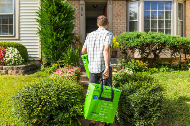 amazon fresh insulated grocery delivery bags totes on front home house porch closeup with man carrying - food logo stock photos and pictures