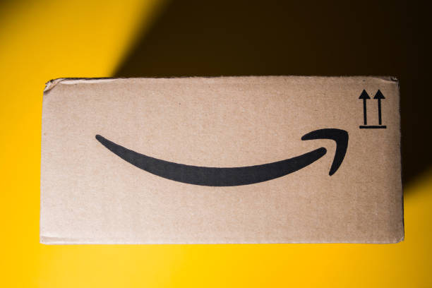 Amazon Prime cardboard box delivery yellow background PARIS, FRANCE - SEP 28, 2018: Directly above view of New Amazon Cardboard box against yellow background. Amazon Prime is the online paid subscription service offered by Amazon.com web-commerce site amazon stock pictures, royalty-free photos & images