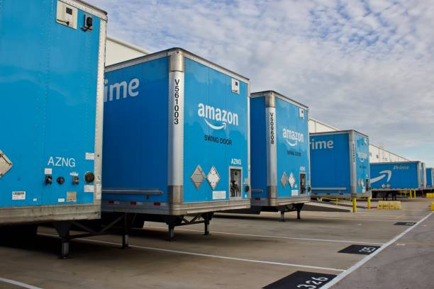 Amazon Prime Trailers at distribution center Miami, Florida August 17,2019 multiple blue Amzon prime trailers backed into bays at a distribution center to unload products for area customers. aerodrome stock pictures, royalty-free photos & images