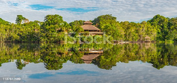 Traditional architecture of an Amazon rainforest lodge in panoramic composition, Yasuni national park, Ecuador. The tributaries of the Amazon river comprise the countries of Suriname, Guyana, French Guyana, Venezuela, Colombia, Ecuador, Peru, Bolivia and Brazil.