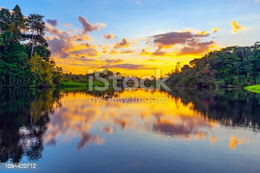 A magic sunset in the Amazon Rainforest inside Yasuni national park. The Amazon rainforest and its tributaries comprise the countries of Ecuador, Peru, Bolivia, Brazil, Colombia, Suriname, Venezuela, Guyana and French Guyana.