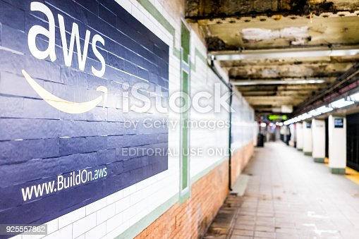 istock Amazon Web Services AWS advertisement ad sign closeup in underground transit platform in NYC Subway Station, wall tiled, arrow, side 925557862