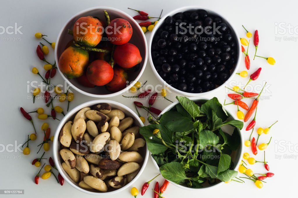 Amazonian food selection: Palm fruits (pupunha), acai berries, brazil nuts, regional herb named jambu, and assorted colorful peppers yellow and red stock photo