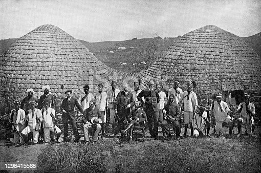 Group of Boer men and AmaZulu chiefs Zulu kraal (village) in the Kingdom of Zululand, South Africa. Vintage photo etching circa 19th century. It was absorbed into the British Colony of Natal in 1897, and then the Union of South Africa in 1910.