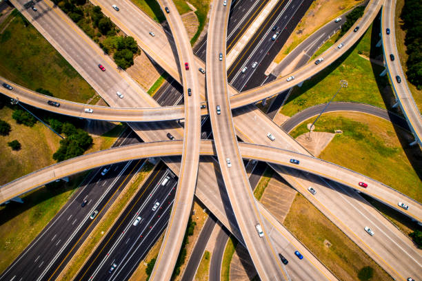 amber abstract aerial straight down view curved highways and interchanges and overpasses aerial drone high above - highway stock photos and pictures