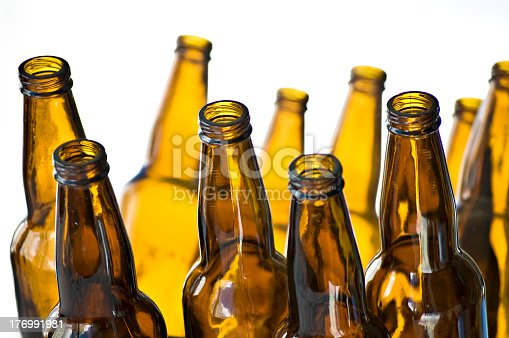horizontal color photograph of a large group of amber colored beer bottles against a white background