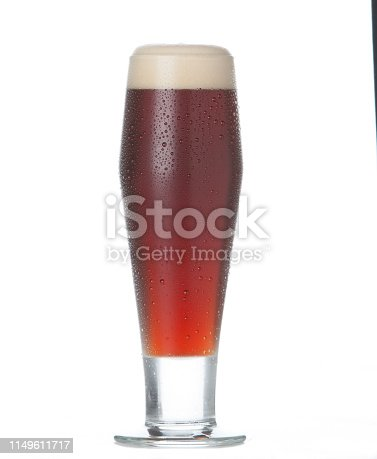 Amber beer in tall pint glass on white background