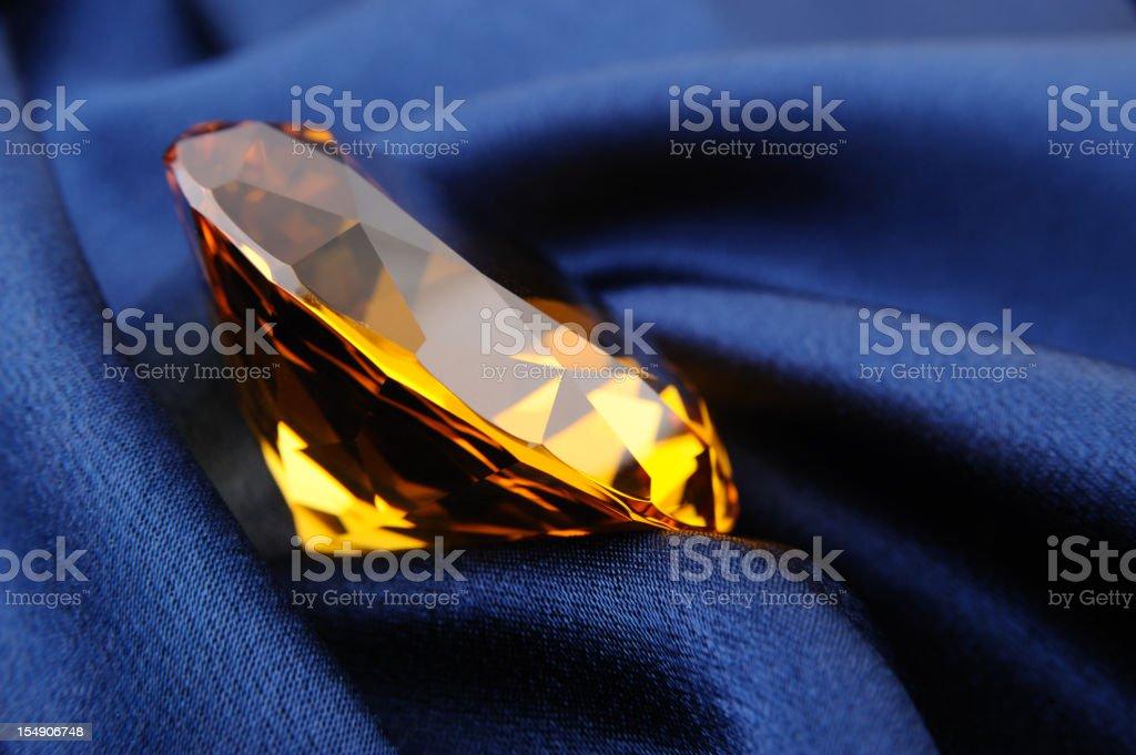 Amber diamond on blue satin royalty-free stock photo