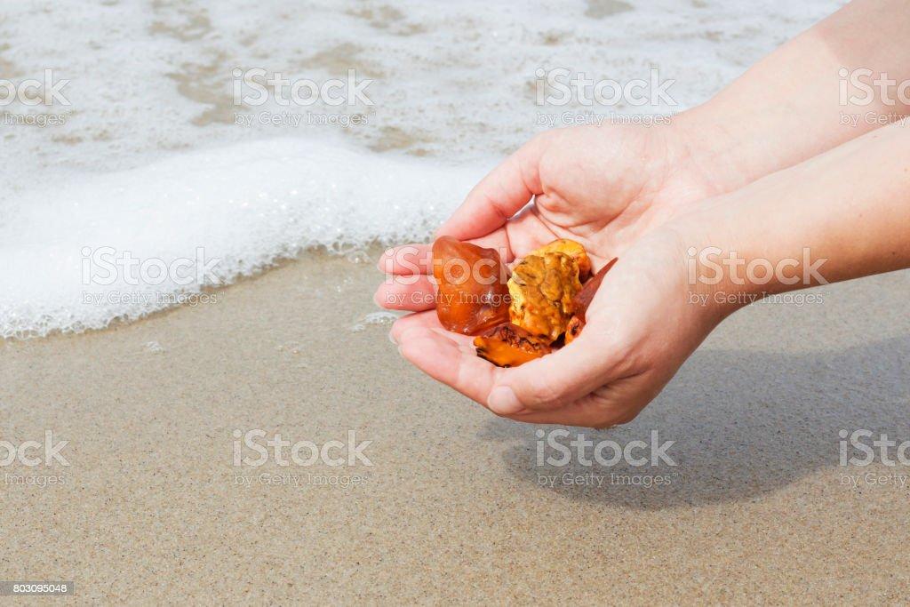 Bernstein in der Hand mit einer hellen Reflexion über die Handfläche vor dem Hintergrund des Meeres. – Foto