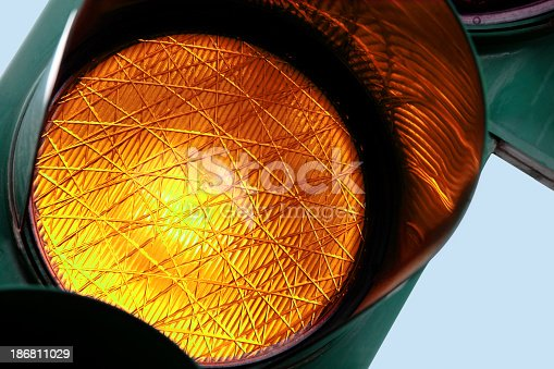 Close-up on an amber traffic light. Other traffic lights in: