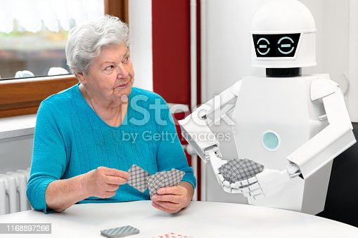 istock ambient assisted living service robot is playing a card game with a senior adult woman, concepts like robotic caregiver in the household or old folks home 1168897266