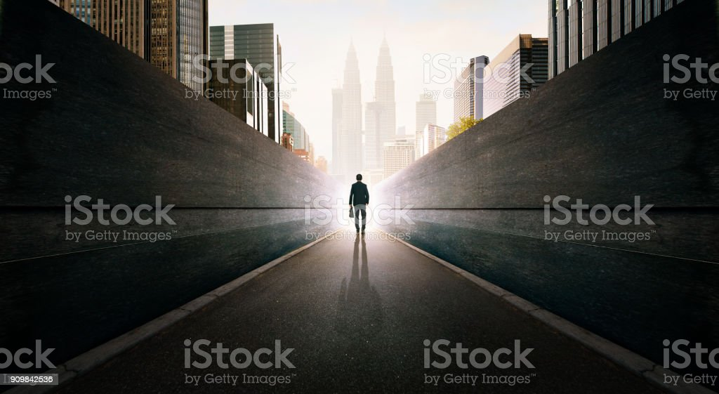 Ambitions concept with businessman walking from alley to modern city . stock photo