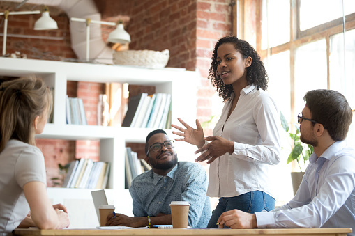 istock Ambitious african black female employee speaking at diverse meeting 1090216744