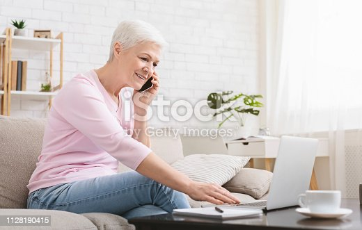 Freelance for any age. Ambitious elderly lady managing project from home, talking on phone and using laptop, copy space