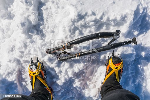 istock Ambitious winter mountain tourism. Two ice axes stuck in the snow at the foot of the high mountain boots with crampons. 1138551166