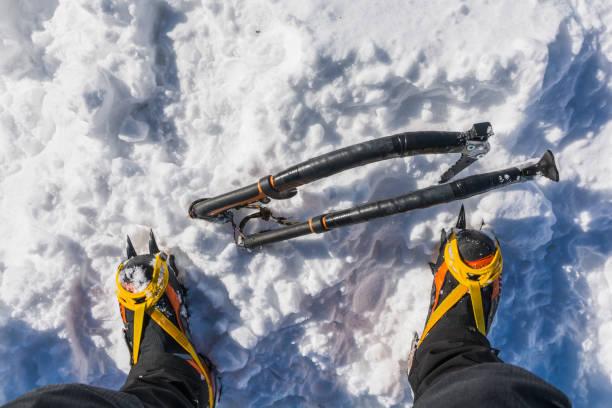 Ambitionierter Winterbergtourismus. Zwei Eisachsen stecken im Schnee am Fuße der Hochhausschuhe mit Steigeisen fest. – Foto