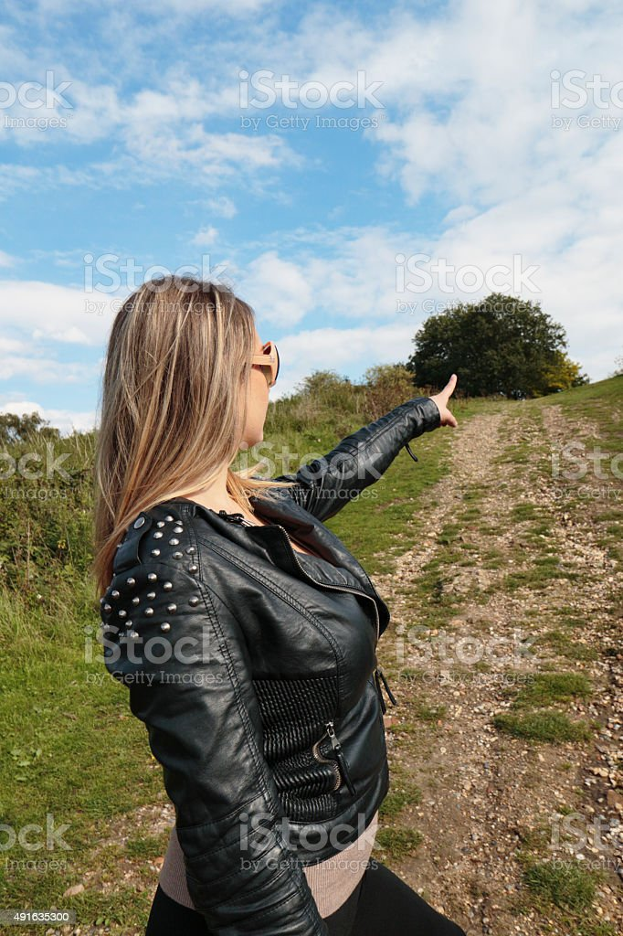 Ambitious woman pointing the way ahead outdoor Polish girl stock photo
