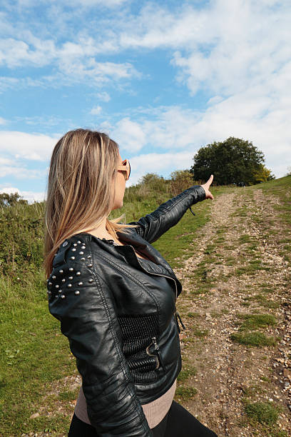 ambitious woman pointing the way ahead outdoor polish girl - whiteway polish outdoor girl stock photos and pictures