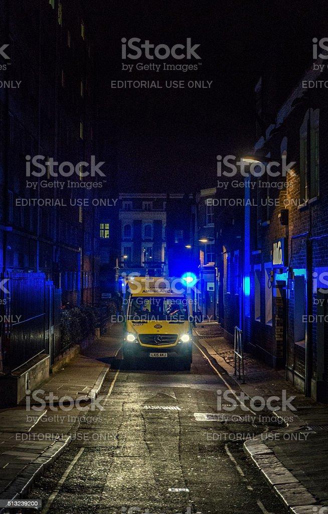 Ambulance at night on narrow city centre street stock photo
