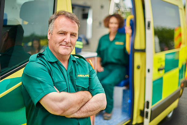 ambulance crew uk ambulance staff members stands next to their ambulance , smiling proudly to camera. They are wearing  green ambulance uniform typical of uk paramedics. ambulance staff stock pictures, royalty-free photos & images