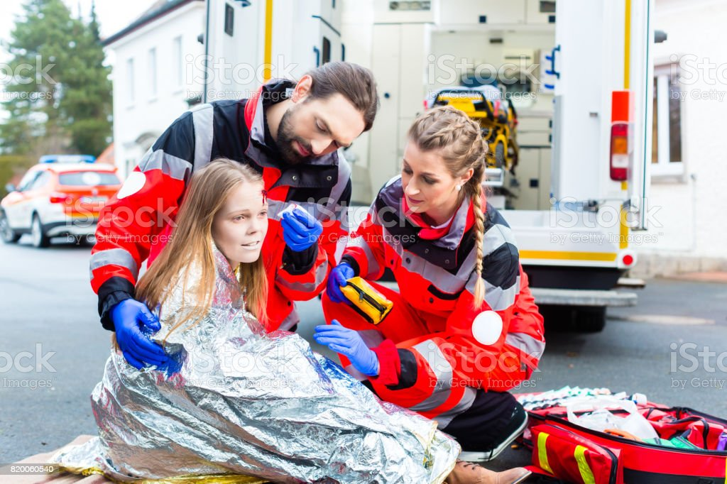 Ambulance doctor helping injured woman stock photo
