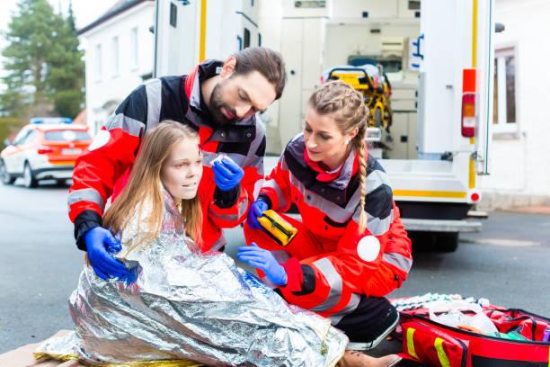Ambulance doctor helping injured woman stock photo