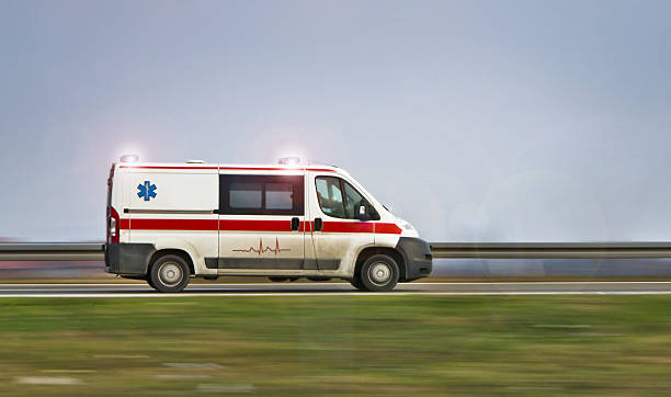Ambulance driving down a road with sirens on stock photo