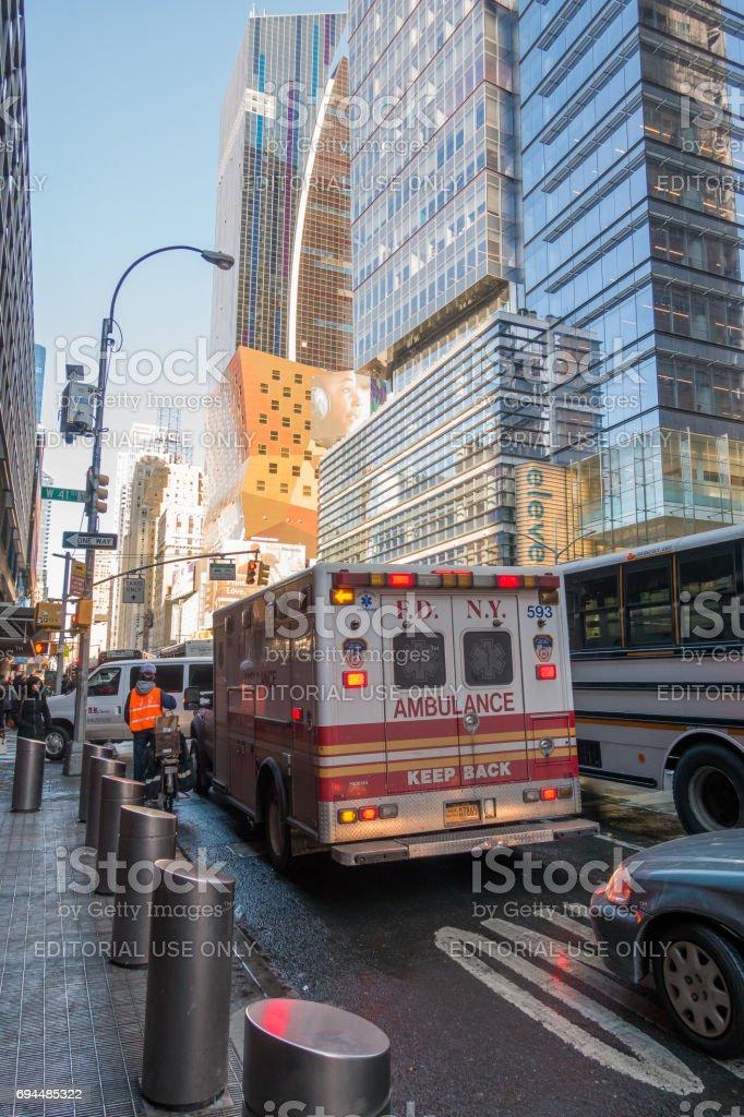 FDNY Ambulance flashing lights siren blasting speed through midtown rush hour traffic in Manhattan. stock photo