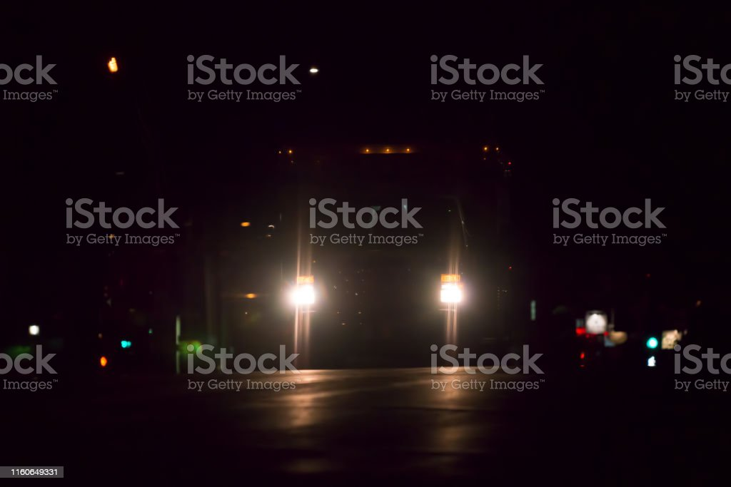 Ambulance headlights on road at night on dark road
