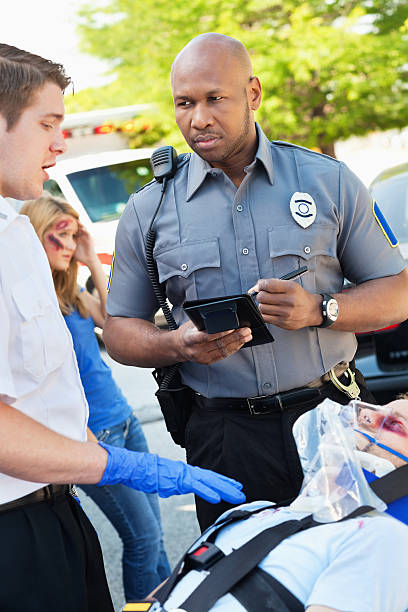 Ambulance medic and police officer discussing accident scene Ambulance medic and police officer discussing accident scene. police interview stock pictures, royalty-free photos & images