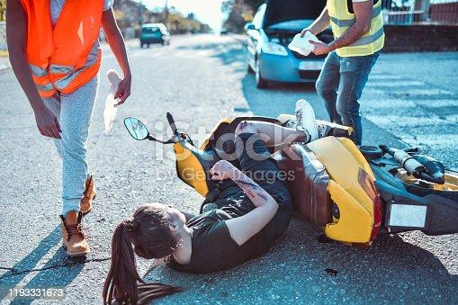 508966965 istock photo Ambulance Paramedics Rushing To Pull Female From Under Motorcycle 1193331673