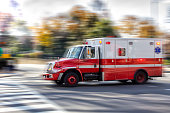 Photo of an red ambulance at a city street. Blurred motion. Urgency. Emergency