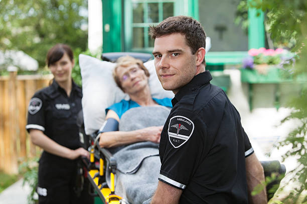 Ambulance Professional Serious ambulance worker with patient on stretcher ambulance staff stock pictures, royalty-free photos & images