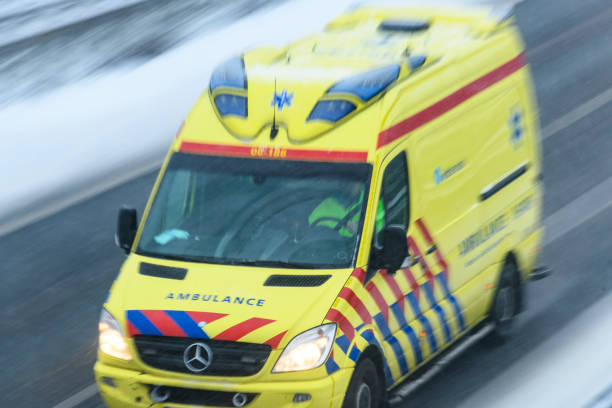 Ambulance rushing to an accident at high speed on a highway during a snow blizzard stock photo