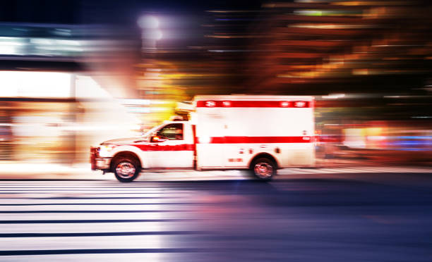 Ambulance speeding at night in New York City Ambulance speeding at night in New York City - motion blur panning action ambulance stock pictures, royalty-free photos & images
