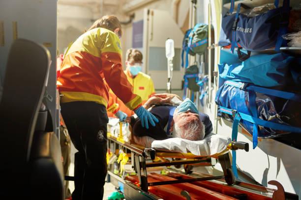 Ambulance Staff Moving Caucasian Senior Man on Stretcher stock photo