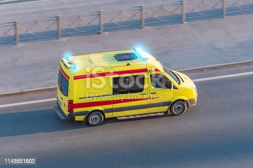 istock Ambulance van fast ride on highway, aerial top view. 1143551602