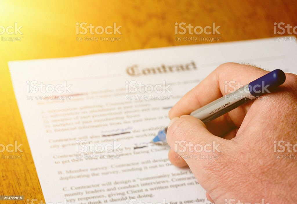Amending a contract. A male hand makes alterations with pen stock photo