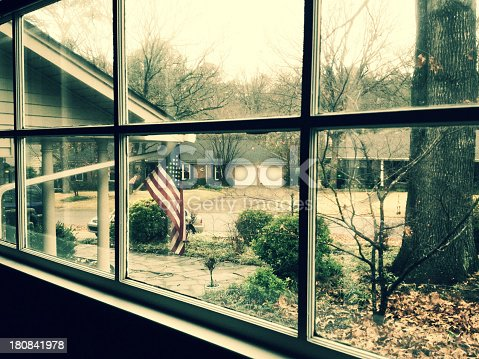 View of an American flag from a window inside looking out.  NOTE:  This image was taken with an iPhone 4s camera app.