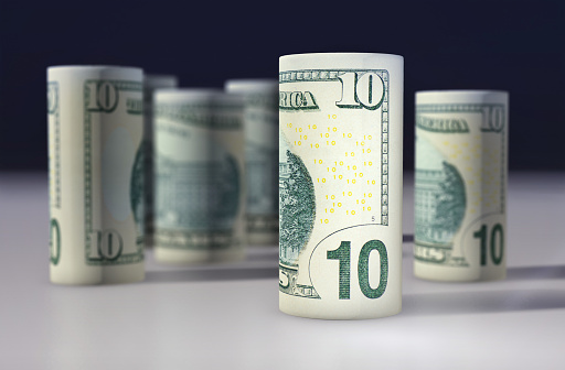 istock American 10 dollars greenback rolled up on the black 645328070
