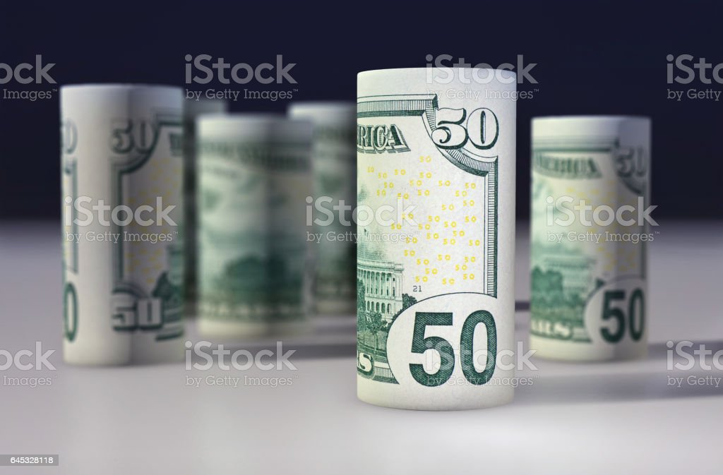 American 50 dollars greenback rolled up on the black stock photo