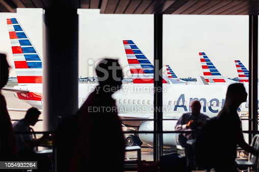 istock American Airlines fleet of airplanes with passengers at O'Hare Airport 1054932264