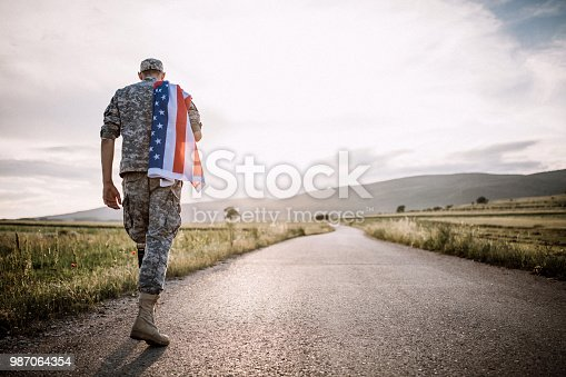 Rear View Of Young Amputee Soldier Walking Road Wearing American Flag