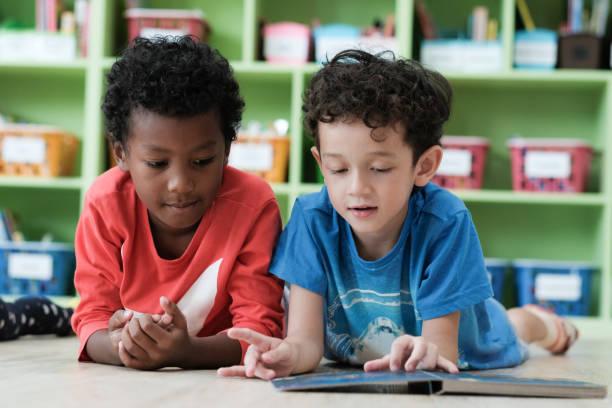 amerikanischen und afrikanischen jungen lesen zusammen mit glück in ihrem kindergarten klassenzimmer, kind bildungskonzept - leseunterricht stock-fotos und bilder