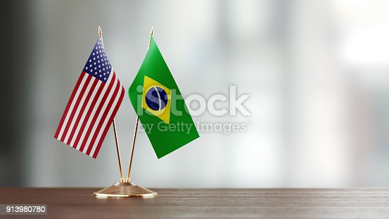 American and Brazilian flag pair on desk over defocused background. Horizontal composition with copy space and selective focus.