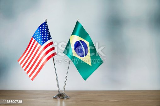 American and Brazilian flag standing on the table with defocused background